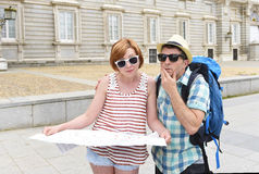 Young tourist couple visiting Europe reading city map looking lost and confused loosing orientation Stock Photo