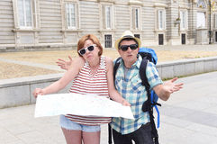 Young tourist couple visiting Madrid in Spain lost and confused loosing orientation Royalty Free Stock Images