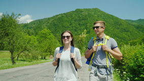 A young tourist couple walks along the road to beautiful mountains covered with forest. Active way of life and vacation. Rear view stock video footage