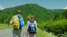 A young tourist couple walks along the road to beautiful mountains covered with forest. Active way of life and vacation. Rear view stock video