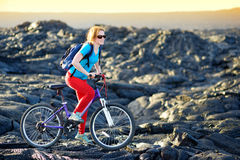 Young tourist cycling on lava field on Hawaii. Female hiker heading to lava viewing area at Kalapana town on her bike. Royalty Free Stock Images