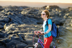 Young tourist cycling on lava field on Hawaii. Female hiker heading to lava viewing area at Kalapana town on her bike. Royalty Free Stock Image
