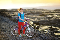 Young tourist cycling on lava field on Hawaii. Female hiker heading to lava viewing area at Kalapana town on her bike. Royalty Free Stock Photography