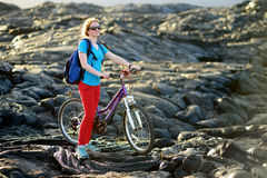 Young tourist cycling on lava field on Hawaii. Female hiker heading to lava viewing area at Kalapana town on her bike. Stock Image