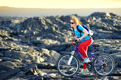 Young tourist cycling on lava field on Hawaii. Female hiker heading to lava viewing area at Kalapana town on her bike. Royalty Free Stock Photo
