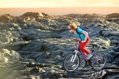 Young tourist cycling on lava field on Hawaii. Female hiker heading to lava viewing area at Kalapana on her bike. Tourist on hike. Young tourist cycling on lava Royalty Free Stock Photo