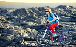 Young tourist cycling on lava field on Hawaii. Female hiker heading to lava viewing area at Kalapana on her bike. Tourist on hike. Young tourist cycling on lava Stock Photo