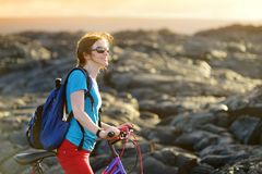 Young tourist cycling on lava field on Hawaii. Female hiker heading to lava viewing area at Kalapana on her bike. Tourist on hike. Young tourist cycling on lava Royalty Free Stock Photography
