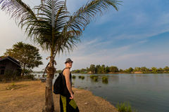 Young tourist on Don Det. Young male tourist walking across Don Det island in south Laos. Landscape of nature on four thousands islands Si Phan Don on Mekhong stock photos