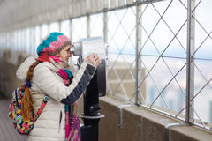 Young tourist enjoying the view of New York though binoculars Royalty Free Stock Photo