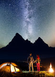 Young tourist family - man and woman holding hands, standing near camp and enjoying amazing starry sky Stock Photo