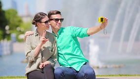 Young tourist friends traveling on holidays in Europe smiling happy. Caucasian couple with city map making selfie. Happy tourist couple, man and woman traveling stock footage