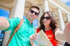 Young tourist friends traveling on holidays in Europe smiling happy. Caucasian family with city map making selfie. Happy tourist couple, men and women traveling stock photos