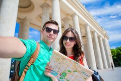 Young tourist friends traveling on holidays in Europe smiling happy. Caucasian family with city map making selfie. Happy tourist couple, men and women traveling stock photo