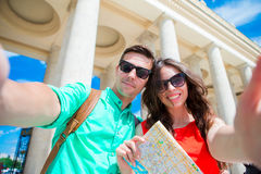 Young tourist friends traveling on holidays in Europe smiling happy. Caucasian family with city map making selfie. Happy tourist couple, men and women traveling royalty free stock images