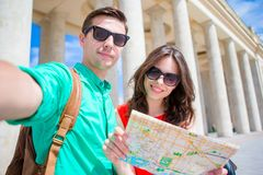Young tourist friends traveling on holidays in Europe smiling happy. Caucasian family with city map making selfie. Happy tourist couple, men and women traveling stock image