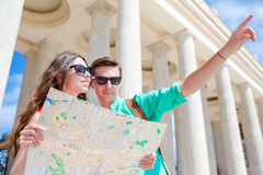 Young tourist friends traveling on holidays in Europe smiling happy. Caucasian family with city map in search of. Happy tourist couple, men and women traveling royalty free stock photography