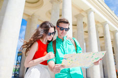 Young tourist friends traveling on holidays in Europe smiling happy. Caucasian family with city map in search of. Happy tourist couple, men and women traveling Stock Photo