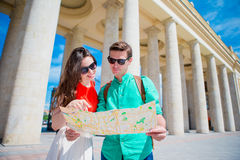 Young tourist friends traveling on holidays in Europe smiling happy. Caucasian family with city map in search of. Happy tourist couple, men and women traveling royalty free stock images