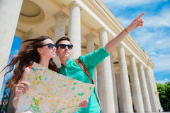 Young tourist friends traveling on holidays in Europe smiling happy. Caucasian family with city map in search of. Happy tourist couple, men and women traveling stock image