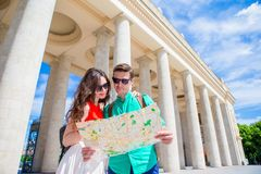 Young tourist friends traveling on holidays in Europe smiling happy. Caucasian family with city map in search of. Happy tourist couple, men and women traveling royalty free stock photo