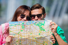 Young tourist friends traveling on holidays in Europe smiling happy. Closeup caucasian family with city map in search of. Happy tourist couple, men and women royalty free stock images