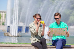 Young tourist friends traveling on holidays in Europe smiling happy. Girl taking photos in the park and man with city Stock Photography