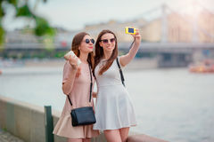 Young tourist friends traveling on holidays outdoors smiling happy. Caucasian girls making selfie background big bridge Stock Photos