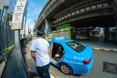 Young tourist gets out of taxi cab, Bangkok. Tourists get out of taxi ready to start shopping Royalty Free Stock Photography