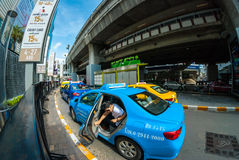 Young tourist gets out of taxi cab, Bangkok. Tourists get out of taxi ready to start shopping Royalty Free Stock Images