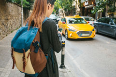 A young tourist girl with a backpack in the big city is watching a mobile application in the phone. Journey. Sightseeing Stock Photo