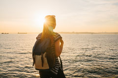 A young tourist girl with a backpack stands next to the sea at sunset and looks into the distance. Rest, relaxation. A young tourist girl with a backpack stands Stock Image
