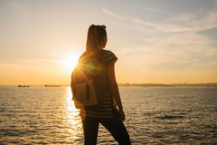 A young tourist girl with a backpack stands next to the sea at sunset and looks into the distance. Rest, relaxation Stock Images