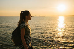 A young tourist girl with a backpack stands next to the sea at sunset and looks into the distance. Rest, relaxation Royalty Free Stock Photography