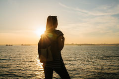 A young tourist girl with a backpack stands next to the sea at sunset and looks into the distance. Rest, relaxation Royalty Free Stock Images