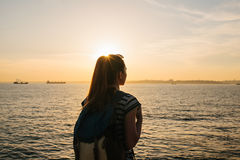 A young tourist girl with a backpack stands next to the sea at sunset and looks into the distance. Rest, relaxation. A young tourist girl with a backpack stands Stock Images
