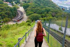 Young tourist girl carrying backpack descending stairs and enjoying the view from Jaragua Peak, Brazil.  royalty free stock image