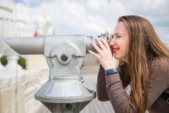 Young tourist girl looking through tower viewer stock photo