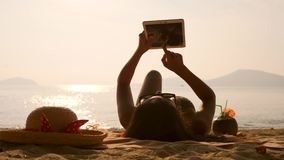 Young Tourist Girl Lying, Sunbathing on Tropical Beach and Using Mobile Tablet Gadget. 4K, Slowmotion. Phuket, Thailand. Young Tourist Girl Lying, Sunbathing on stock video footage