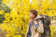 Young girl tourist, walking through a forest with a big backpack on her back. stock images