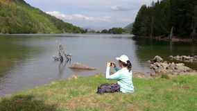 Young tourist girl sitting next to the mountain lake and take a picture with mobile phone.  stock video footage