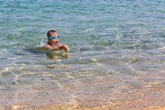 Young tourist girl in swimming sports glasses is floating in the Aegean Sea on the coast of Sithonia Peninsula. Young tourist girl in swimming sports glasses is Stock Image