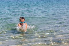 Young tourist girl in swimming sports glasses is floating in the Aegean Sea on the coast of Sithonia Peninsula Stock Photo