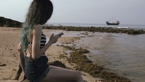 Young Tourist Girl Using Mobile Phone at the Beach near the Sea with Beautiful boat . stock video