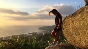 Young Tourist Girl Watching Amazing Sunset at the Viewpoint. Slow motion travel motivation video. Phuket, Thailand. stock video footage