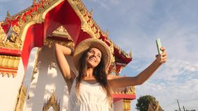 Young Tourist Girl in White Dress and Big Straw Hat Taking Selfie Photo with Mobile Phone at Thai Buddhist Temple. Phuket, Thailand. 4K, Slowmotion stock video footage