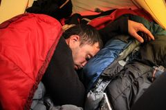 Young tourist guy sleeps deep in a sleeping bag royalty free stock images