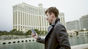 Young tourist is having a video chat over the cellphone in front of the Bellagio hotel stock video footage
