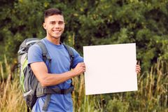 Young tourist hiking alone. Traveling. Portrait of a young handsome tourist wearing blue t-short and backpack standing looking at the camera smiling and holding Stock Photo