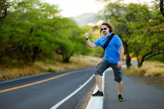 Young tourist hitchhiking along a road. Young tourist with a backpack hitchhiking along a road Royalty Free Stock Image